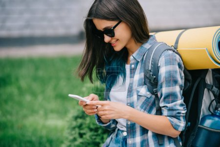 smiling young woman with backpack using smartphone