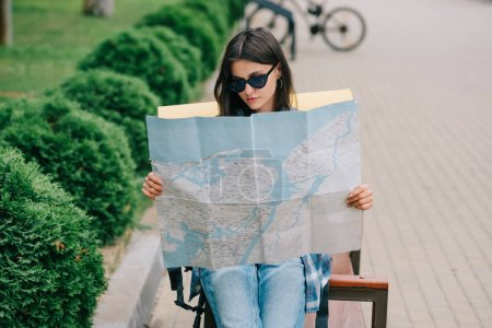 young woman traveler in sunglasses holding map