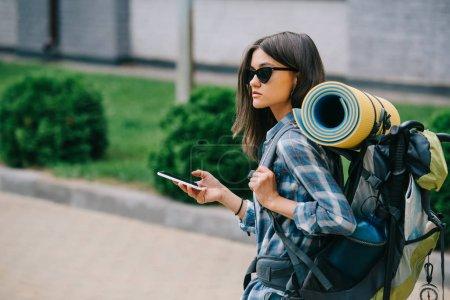 Photo pour Jeune femelle backpacker à lunettes de soleil maintenant smartphone - image libre de droit