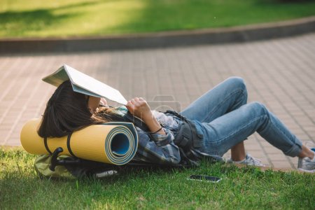 Photo for Girl holding map on face while lying with backpack on grass - Royalty Free Image