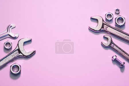 top view of wrenches, nuts and screw on pink surface