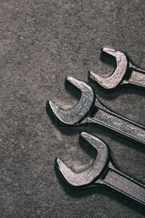 top view of three metal wrenches on grey surface