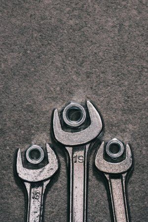 top view of wrenches and nuts on grey surface