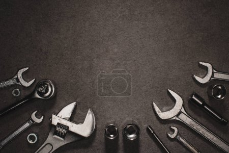 flat lay with different wrenches, monkey wrench and nuts on grey surface