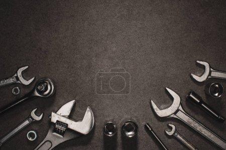 flache Verlegung mit verschiedenen Schlüsseln, Affenschlüsseln und Muttern auf grauer Oberfläche