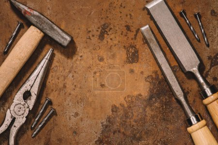 flat lay with old shabby mechanical tools on brown surface