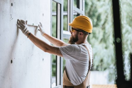 Photo for Side view of builder in protective helmet and googles using spirit level at construction site - Royalty Free Image
