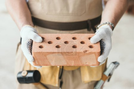 cropped image of builder in protective gloves holding brick