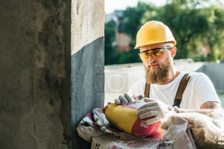 builder in protective googles and hardhat opening bag of cement at construction site
