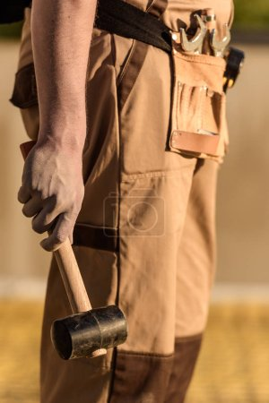 partial view of construction worker in uniform holding hammer