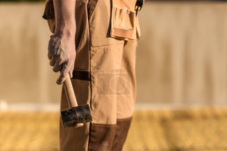 cropped image of construction worker in uniform holding hammer