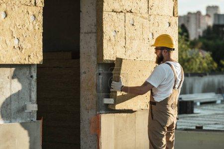 Foto de Vista lateral del constructor en casco protector y googles haciendo aislamiento de la pared en el sitio de construcción - Imagen libre de derechos