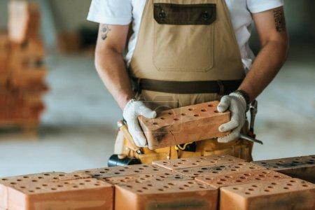 Photo pour Image recadrée d'un travailleur de la construction portant des gants de protection tenant de la brique sur le chantier - image libre de droit