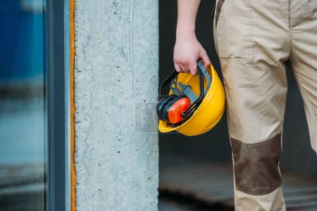cropped image of builder in uniform holding construction headphones and protective helmet