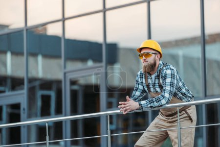 young builder in protective googles and hardhat holding hands together near building