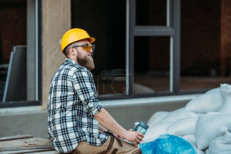 side view of builder in protective googles and hardhat resting with bottle of water at construction site