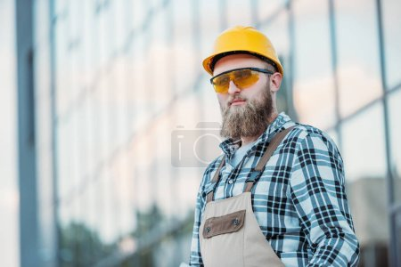 selective focus of construction worker in protective googles and hardhat looking away