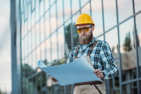 construction worker in protective googles and hardhat looking at blueprint