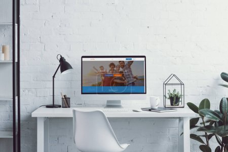 computer with loaded couchsurfing page on table in modern office