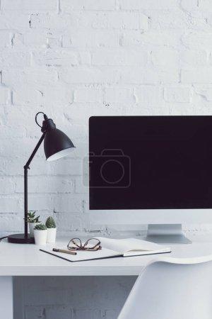 Photo pour Ordinateur avec écran blanc et verres sur ordinateur portable sur la table dans l'espace de travail moderne - image libre de droit