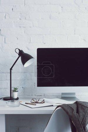 Photo pour Ordinateur avec écran blanc et la lampe sur la table dans l'espace de travail moderne - image libre de droit