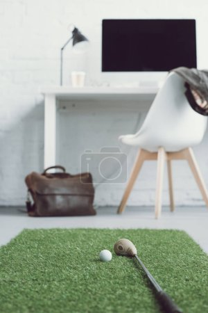 golf club and ball on green grass carpet in light modern office
