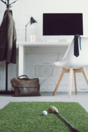 golf club and ball on green grass carpet in modern workplace