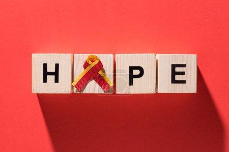 vue du haut du ruban et lettrage espoir de cubes en bois sur fond rouge, concept de journée mondiale de l'hépatite