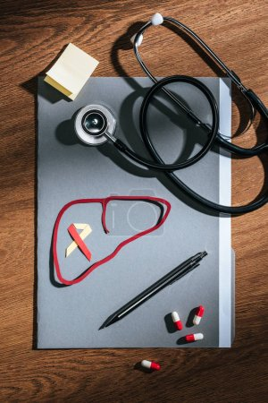 top view of folder, pills, stethoscope, empty stick it and liver with ribbon on table, world hepatitis day concept