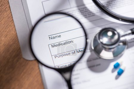 view from magnifier on medical questionnaire on table with stethoscope and pills
