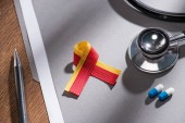 selective focus of ribbon, stethoscope, pills and folder with pen on table, world hepatitis day concept