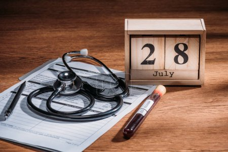 Photo for Selective focus of test flask with blood sample, stethoscope, medical questionary and wooden calendar with 28th july date on table, world hepatitis day concept - Royalty Free Image
