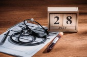 selective focus of test flask with blood sample, stethoscope, medical questionary and wooden calendar with 28th july date on table, world hepatitis day concept
