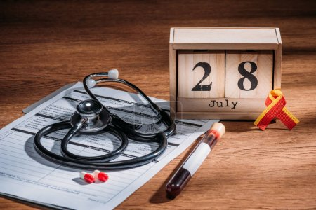 selective focus of wooden calendar with 28th jule date, medical questionnaire, pills, stethoscope, test flask with blood sample, world hepatitis day concept