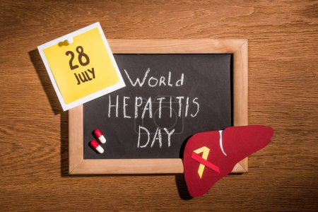 Photo for Top view of blackboard with lettering world hepatitis day, liver, pills and stick it with lettering 28th july on table - Royalty Free Image