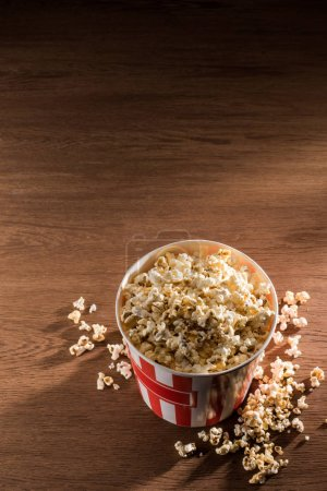 Photo for Close up view of disposable bucket with popcorn on wooden tabletop - Royalty Free Image