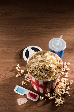 close up view of paper bucket with popcorn, soda drink, 3d glasses and retor cinema tickets on wooden tabletop