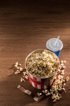 close up view of paper bucket with popcorn, soda drink and retro cinema tickets on wooden tabletop