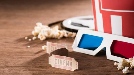 close up view of paper bucket with popcorn, retro cinema tickets and 3d glasses on wooden tabletop