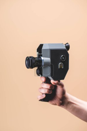 Photo for Cropped shot of man holding retro camera in hand isolated on beige - Royalty Free Image