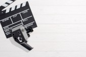 flat lay with clapper board and retro camera on white wooden tabletop
