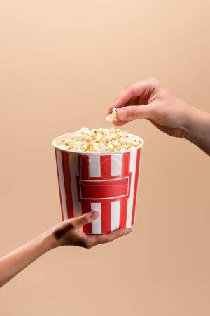 Photo pour Recadrée coup de mains mâles et femelles avec godet jetable avec pop-corn isolé sur beige - image libre de droit