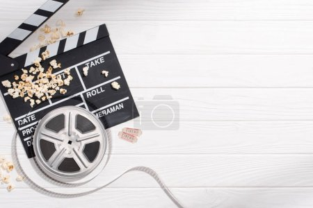 Photo for Flat lay with clapper board, filmstrips, popcorn and retro cinema tickets arranged on white wooden tabletop - Royalty Free Image