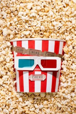 flache Liege mit Anordnung eines Einwegeimers mit Popcorn, Retro-Kinokarten und 3D-Gläsern