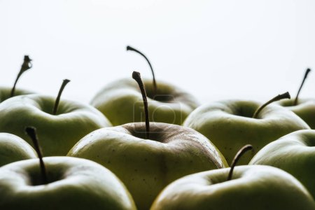 close up view of ripe green apples on white backdrop