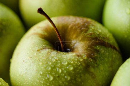 selective focus of water drops on green apples backdrop