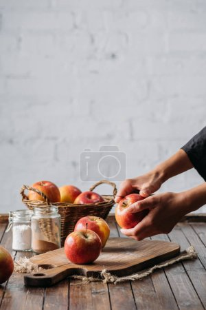 partial view of woman peeling apple with knife