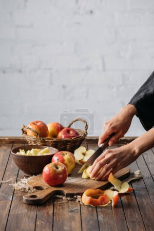 cropped shot of woman cutting apples on wooden cutting board