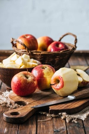 close up view of peeled, cut and wholesome apples on cutting board on dark wooden surface