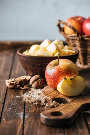 Photo pour Bouchent la vue de pommes coupées et salutaire sur la planche à découper sur une surface en bois sombre - image libre de droit